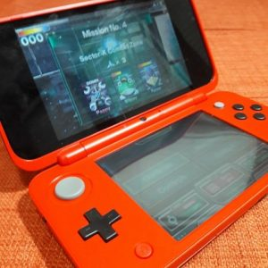 Red Poke Ball edition 2DS XL handheld with graphics from the Star Fox game on both screens against orange background.