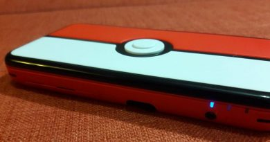 The top of a Red 2DS XL handheld against an orange background.