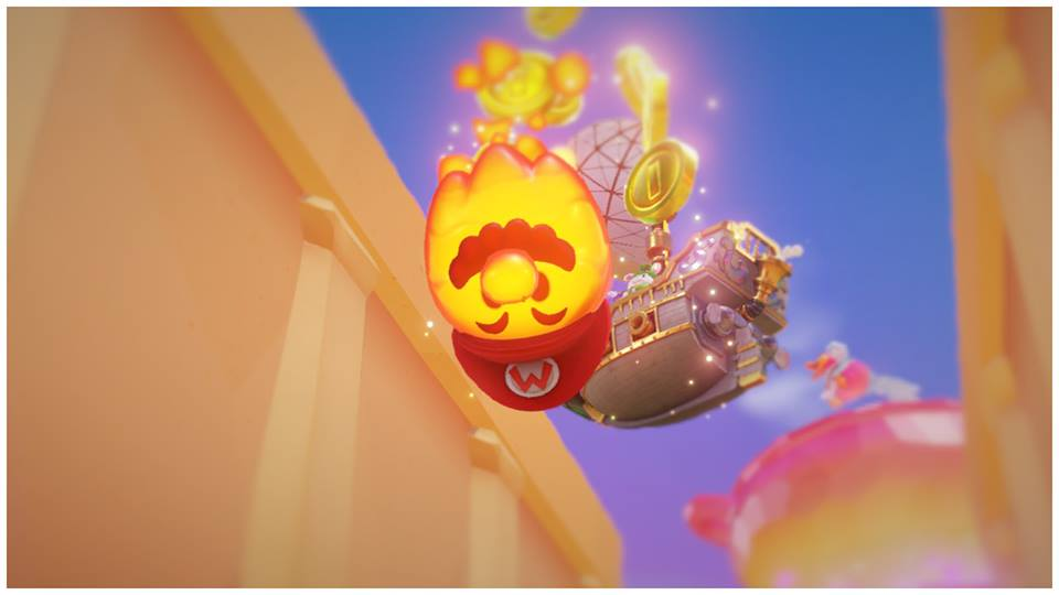Picture from Super Mario Odyssey. A orange fireball falling down in the center. The fireball has a brown mustache, and a red cap with a M in the center.